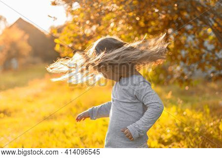 Cute Caucasian Little Girl In The Country. Kid Waved Her Head, Hair Flew. Hair Flare In The Rays Of