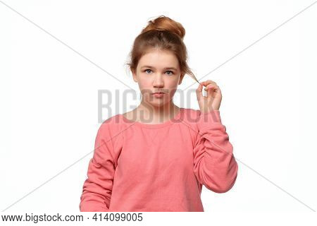 Young Girl 12-14 Years Old With Bun Hairstyle Curling Strand Of Hair On Finger, Looking Thinking, Ha