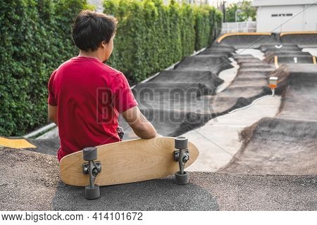 Asian Man Sitting With Surfskate Or Skate Board In Pumptrack Skate Park When Sunrise Time Over Photo