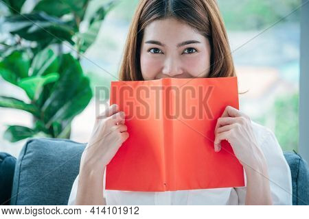 Relax Asian Woman Reading Book Sitting On Sofa In Living Room Holding Book To Read. Young Woman Rela