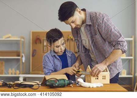 Little Boy And His Dad Making Wooden House Model As Part Of School Homework Project