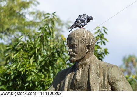 Statue Of Soviet Leader Lenin. There's A Pigeon On His Head. Sunny Summer Day. Side View. Crimea, Su