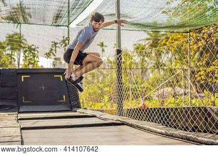 Young Man On A Soft Board For A Trampoline Jumping On An Outdoor Trampoline, Against The Backdrop Of