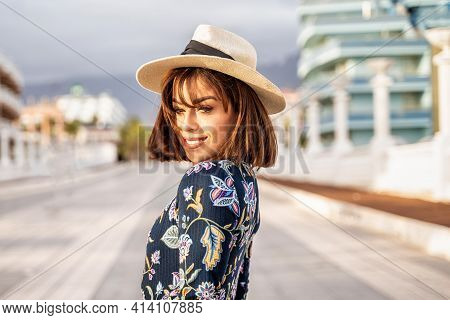 Smiling Pretty Girl Wearing Summer Hat, Looking At Camera While Walking On The City Street. Cute Lat