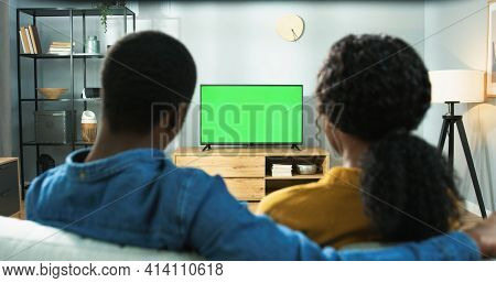 Close Up Of Wife And Husband Sitting At Home Together Watching Tv With Chroma Key. Back View Of Afri
