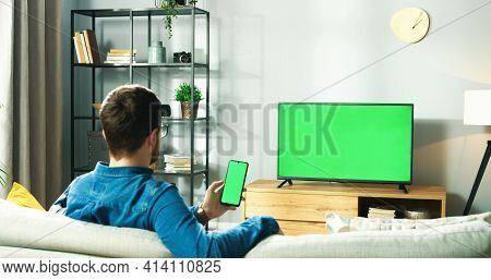 Rear Of Caucasian Young Man In Glasses Sitting On Couch In Living Room At Home Watching Tv With Gree