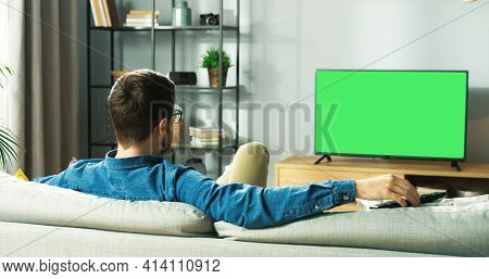 Rear Of Caucasian Young Guy Watching Tv With Chroma Key Resting On Sofa Sitting In Living Room In Ho