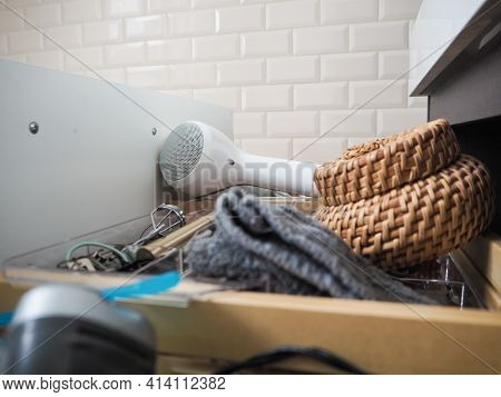 Messy Open Bathroom Drawer With Electric Shaver, Facecloth, Container And Hairdryer