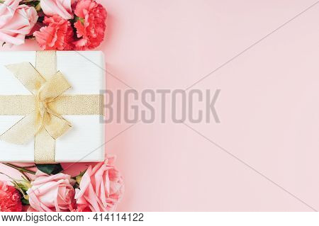 Beautiful Bouquet Of Roses With Gift Against Pink Background. Free Space For Text