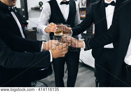 Promising Young Men Celebrate And Drink Whiskey. Best Men With Glasses Filled Up With Alcohol Drinks