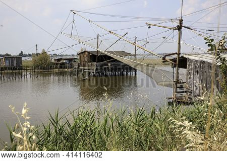 Po River (fe),  Italy - April 30, 2017: An Old Fisherman\'s House With A Net On Po River, Delta Regi
