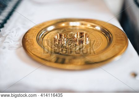Wedding Rings In The Church. Wedding Rings Stand On Glass Box On Table In Church. Two Golden Wedding