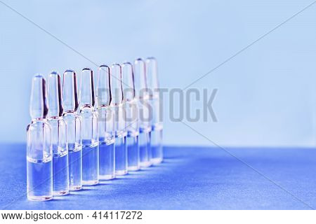 Medical Ampoules For Injection On A Blue Background. Scattered Glass Ampoules With Medicine On The T