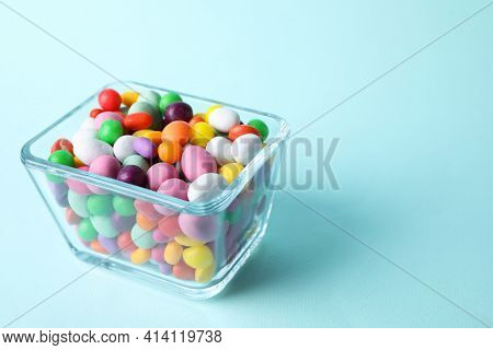 Yummy Candies In Glass Bowl On Light Blue Background, Space For Text