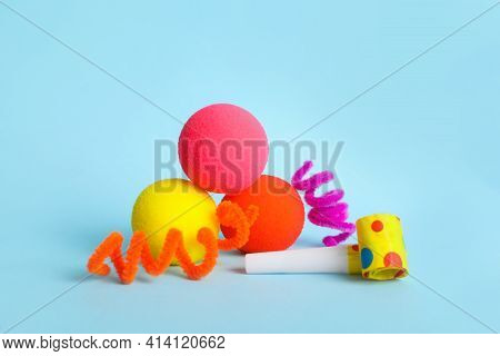 Clown Noses, Party Blower And Fluffy Wires On Light Blue Background