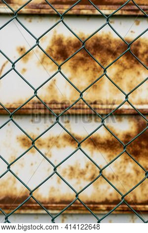 Steel Green Fence Mesh Chain Link And Old Rusty Metal Wall In Blur On The Background