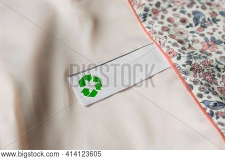 Clothing Label With Recycling Symbol On Light Garment, Closeup
