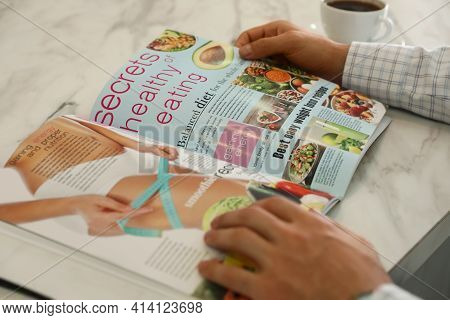 Man Reading Culinary Magazine At White Marble Table, Closeup