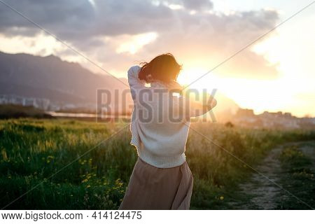 Portrait From Back Of A Young Woman Or Girl On Very Green Meadow Watching The Sunset Enjoying Nature