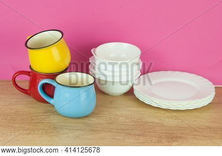 Set of various colorful dishware and cutlery on wooden table