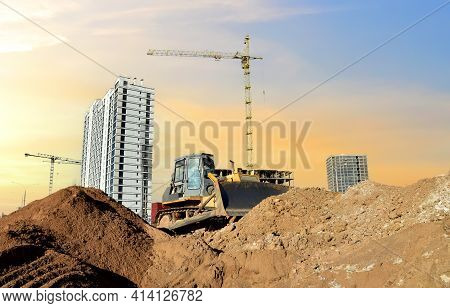 Dozer On Earthmoving At Construction Site On Sunset Background. Construction Machinery And Equipment