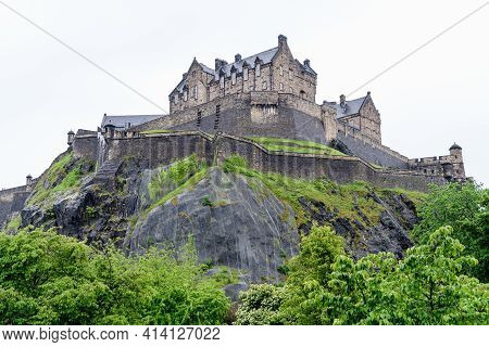 Edinburgh Castle, Scotland And Old Green Trees, As Seen From Princes Street Gardens In A Cloudy Rain