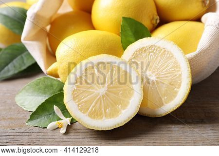 Many Fresh Ripe Lemons With Green Leaves And Flower On Wooden Table, Closeup
