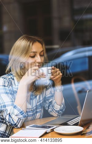A Young Blonde Woman Sitting In Cafe With Cup Of Coffee And Laptop. View Through The Window. Telewor