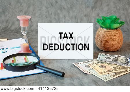 Tax Deduction Is Written In A Document On The Office Desk With Office Accessories, Money And Diagram