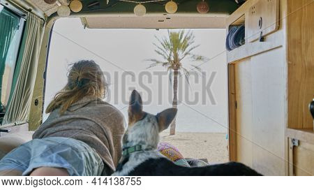girl and her dog on a bed of a self converted camper van looking through the window living van life