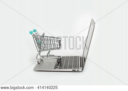 Online Shopping Concept With Laptop Computer And Shopping Cart Isolated On White Background With Cop