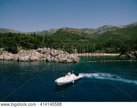 A Wealthy Man Drives A Sports Boat Against The Backdrop Of A Luxury Villa And Beach In An Expensive