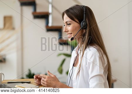 Happy Employee Woman With Headphones Looking At Laptop Computer Screen, Helping Customers Remotely,