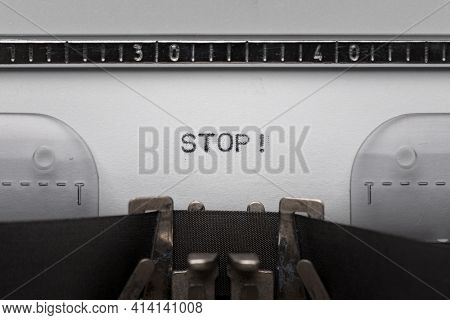 Typing text STOP on vintage manual typewriter. Close up of writes word on white paper. Shot in macro.