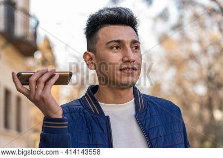 Young Latino Man Listening To An Audio Message With His Smartphone Outdoors