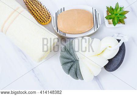 Herb Soap, Shower Sponge And Shampoo Pump Bottle Inside A Bright Bathroom Background.