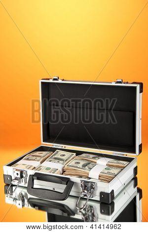 Suitcase with 100 dollar bills on orange background