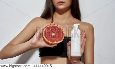 Close Up Shot Of Model Girl With Grapefruit And Skin Gel. Brunette Standing In A Light Studio With A