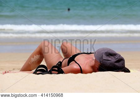 Woman In Bikini Lying And Sunbathing On A Sandy Beach On Sea Background, Tanned Skin Is Covered By S
