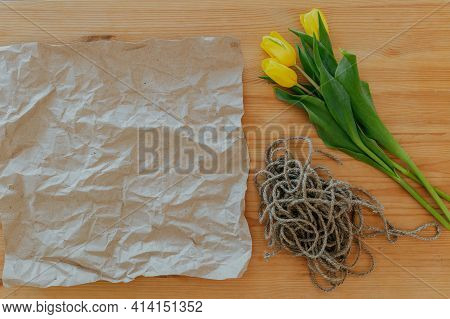 Bright Fresh Yellow Tulips On Wooden Background. Packing Of Flowers Into Kraft Paper. Rope, Bunch Of