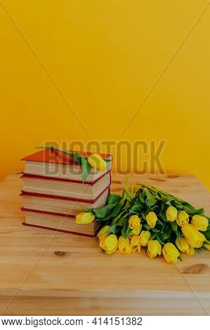 Bright Fresh Yellow Tulips On Yellow Background. Bunch Of Tulips And Many Books. Flowers On Pile Of