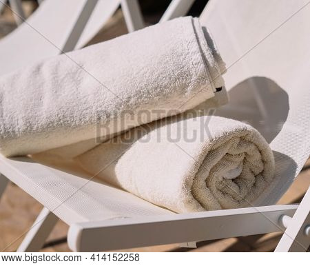 Chair In A Hotel Pool With Two Perfectly Folded White Towels