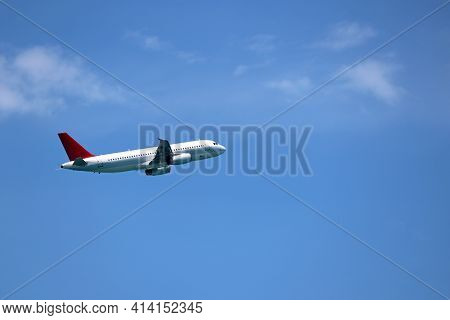 White Airplane Flying In The Blue Sky With Clouds. Commercial Plane Gaining Altitude, Side View