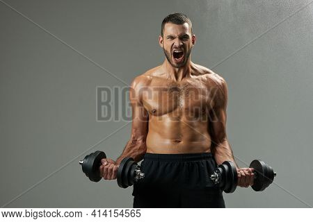 Exited Handsome Bodybuilder With Powerful Torso Building Up Muscles With Dumbbells In Room Indoors