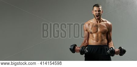 Website Header Of Exited Handsome Bodybuilder With Powerful Torso Building Up Muscles With Dumbbells