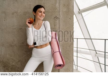 Young smiling woman holding yoga mat while standing with yoga mat indoors