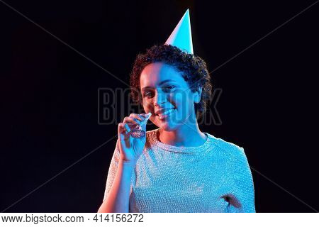 african woman in party cap with blower over black