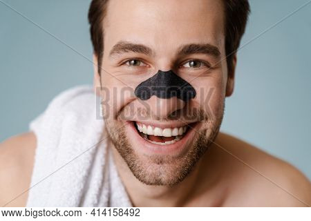 Close up of a brunette shirtless man with stubble wearing nose patch against blackheads standing over blue wall