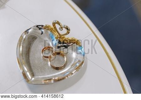 Wedding Day. Gold Wedding Rings On A Gold Saucer, Solemn Ceremony At A Wedding, Close-up.happy Day.