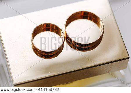 Wedding Day. Gold Wedding Rings On A Gold Background Of A Bottle Of Women's Perfume, Details At The